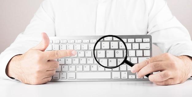 コンピューターまたはラップトップの虫眼鏡と白いキーボードを持つ男。ウェブ検索、情報閲覧の概念。