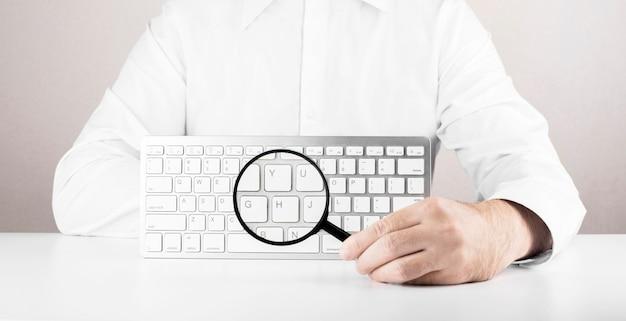 コンピューターまたはラップトップの拡大鏡と白いキーボードを持つ男