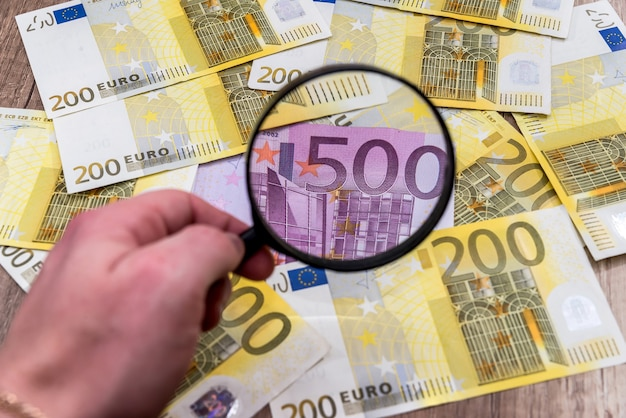 Man with magnifying glass find euro notes