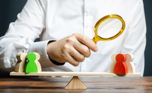 A man with a magnifying glass is looking at the rival red and green figures groups on scales