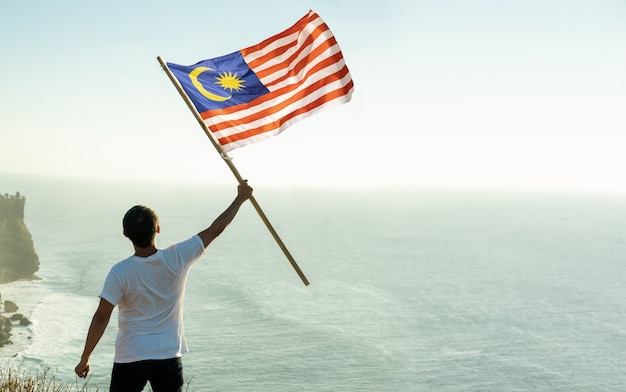 Человек с малайзийским флагом малайзии на вершине горы