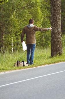 지도와 가방을 손에 들고 길가에 걷는 남자