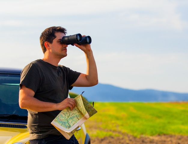 Man with map and binoculars at countryside