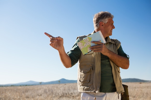風景の上に立っている間指す地図を持つ男