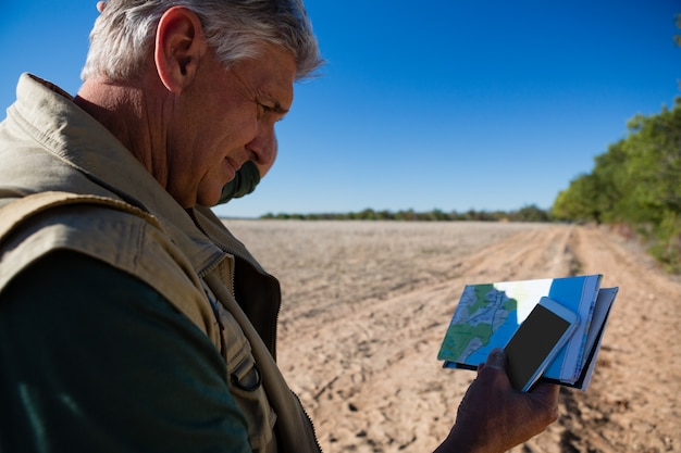Man with map using phone on field