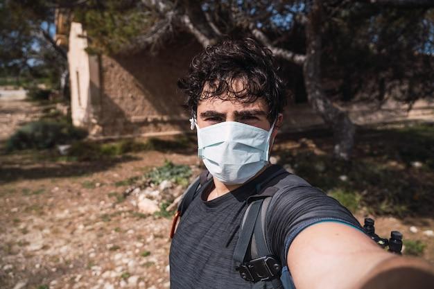 森の中で自分撮りをするマスクとバッグを持つ男