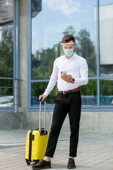 Человек с маской и мобильным телефоном проверки багажа