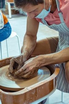 마스크를 든 남자가 도자기 작업장에서 점토 컵을 만듭니다.