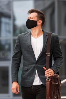Uomo con la maschera durante una pandemia mentre va al lavoro