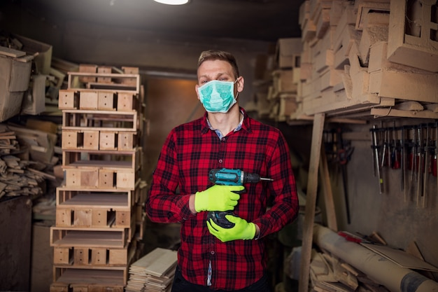 Man with mask on face working in workshop