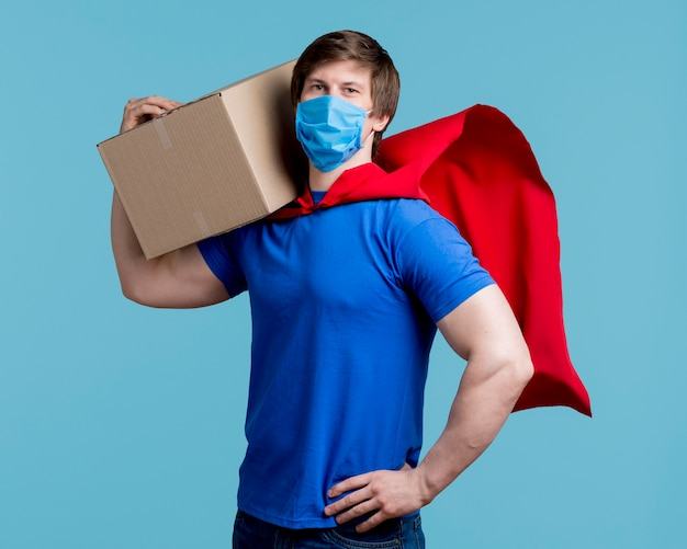 Man with mask holding box