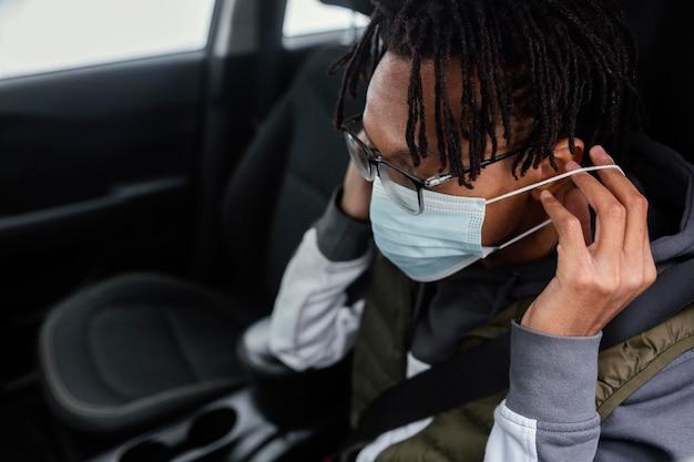 車の中でマスクを持つ男