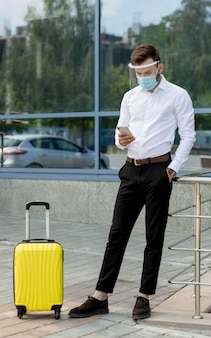 Man with mask and luggage using mobile