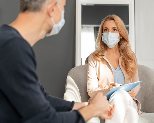 Man with mask talking to woman counselor