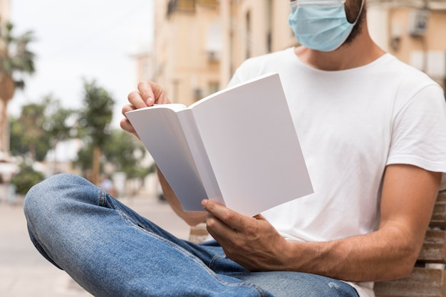 Man with medical mask on bench reading book