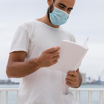 Man with medical mask by the lake reading book