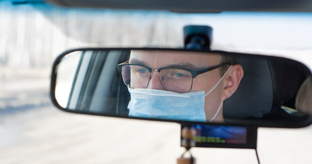 Man with medical mask and glasses driving