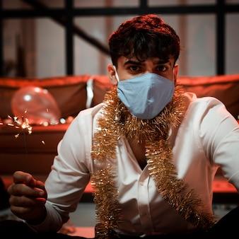 Мужчина с медицинской маской держит бенгальский огонь на новогодней вечеринке
