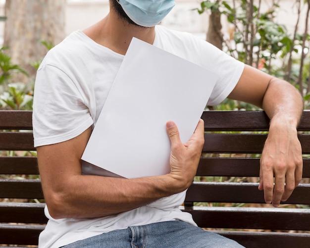 ベンチに本を保持している医療マスクを持つ男