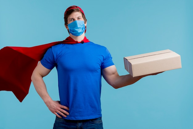 Man with medical mask holding box