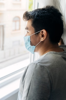 Man with medical mask at home during the pandemic looking through the window