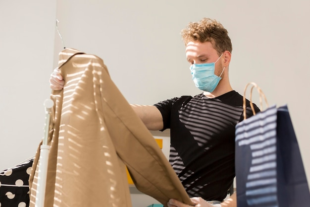 Man with medical mask looking at clothes