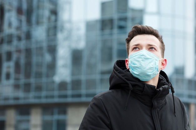 Man with medical mask posing in the city with copy space