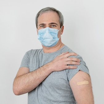 Man with medical mask showing bandage on arm after vaccination