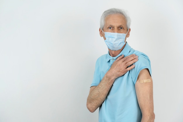 Man with medical mask showing bandage on arm after vaccine shot