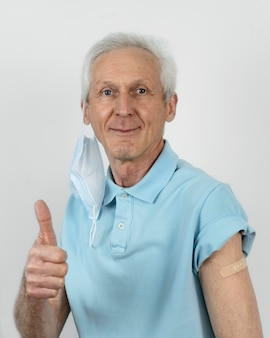 Man with medical mask showing thumbs up with bandage on arm after vaccine shot