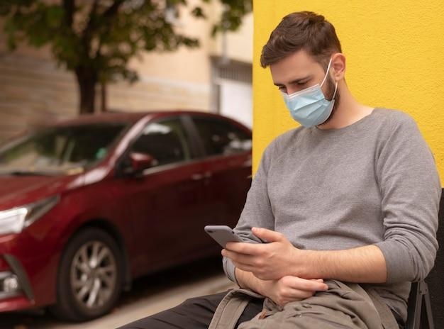 Человек с медицинской маской, сидя на скамейке