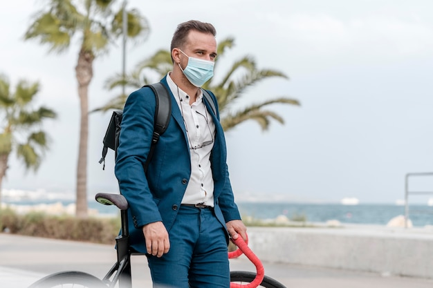 그의 자전거 옆에 서있는 의료 마스크를 가진 남자