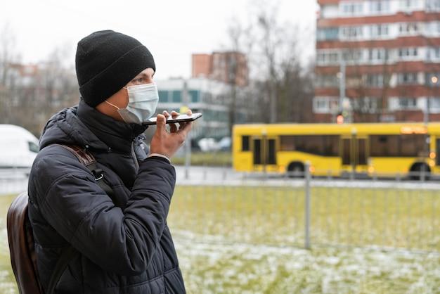 市内の電話で話している医療マスクを持つ男