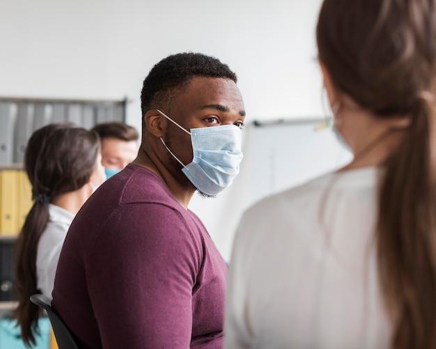 Uomo con maschera medica che lavora in ufficio durante la pandemia