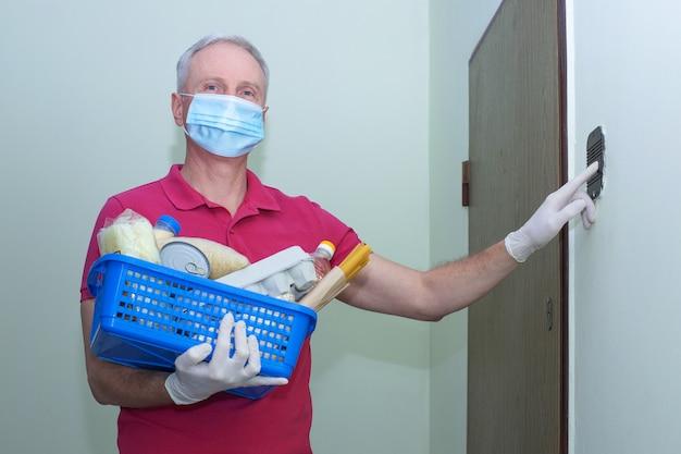 Человек с медицинской хирургической маской звонит в дверь, так что пожертвование пищи.