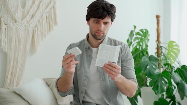 약물을 가진 남자는 침실의 침대에 앉아 약물의 의학적 사용 지침을 읽었습니다.