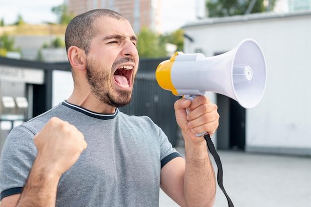 Человек с мегафоном кричит в знак протеста