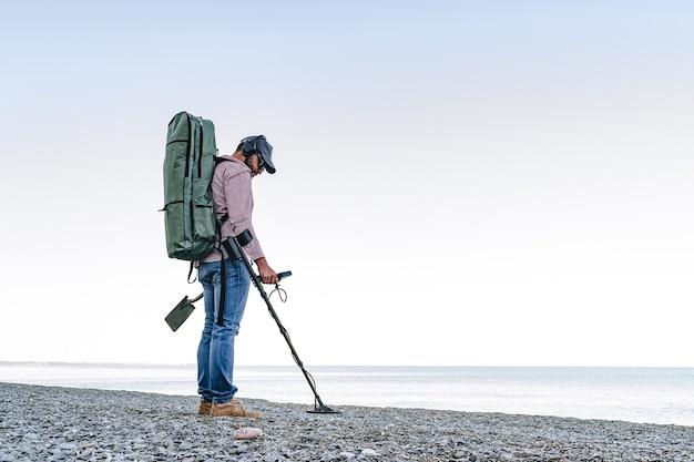 Человек с устройством металлоискателя ищет потерянные сокровища на пляже