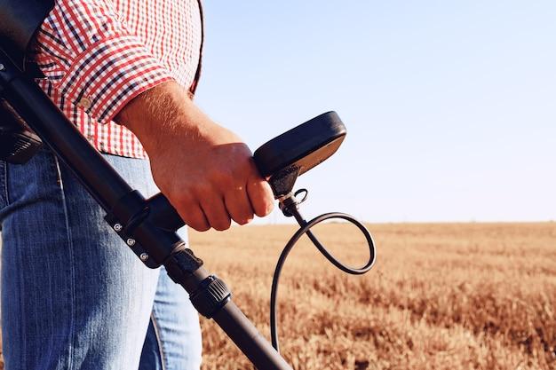 Человек с металлоискателем ищет металлические товары в поле утром