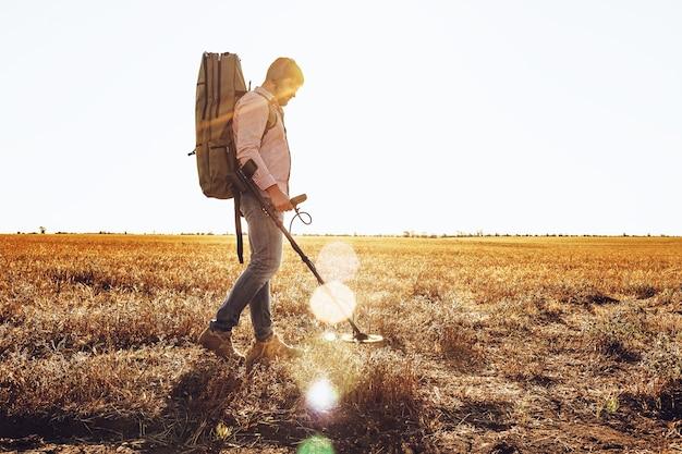 Человек с металлоискателем в поисках металлических изделий в поле