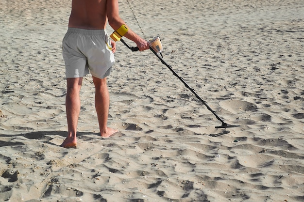 Man with a metal detector on a sea sandy beach in summer day