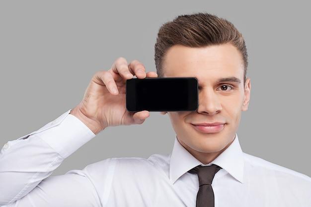 모바일을 가진 남자입니다. 셔츠와 넥타이를 매고 눈 앞에 휴대폰을 들고 회색 배경에 서서 웃고 있는 잘생긴 청년