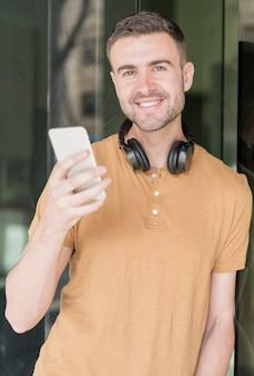Человек с мобильным телефоном и наушниками