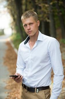 秋の公園で携帯電話を持つ男。屋外のスマートフォンを持つビジネスマン。ソーシャルネットワークのブログとウェブログ。現代の生活とビジネスコミュニケーションのための新技術。