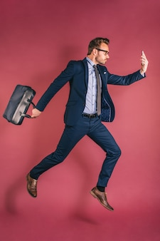 Человек с мобильным телефоном прыгает с портфелем