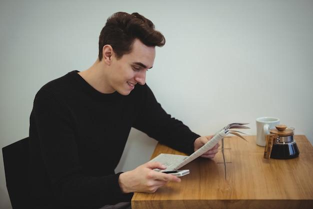 Человек с мобильным телефоном читает газету