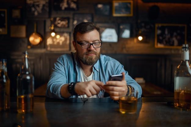 Человек с мобильным телефоном, сидя за стойкой в баре. один мужчина отдыхает в пабе, человеческие эмоции, досуг, ночная жизнь