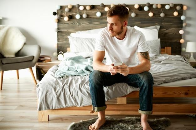 ベッドに座っている携帯電話を持つ男