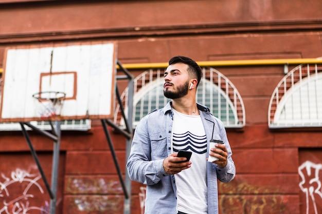 バスケットボールコートに立っている携帯電話の男