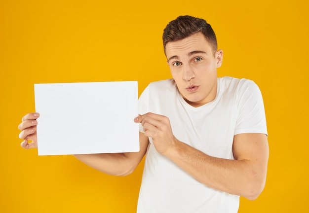 Man with mockup white sheet of paper business card business yellow wall.